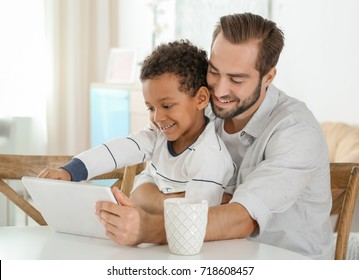 Happy father with adopted African-American boy using tablet computer at home