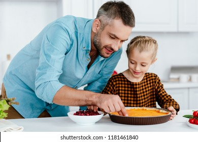 happy father and adorable little daughter decorating pumpkin pie for thanksgiving day
