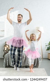 happy father and adorable little daughter in pink tutu skirts dancing and smiling at camera