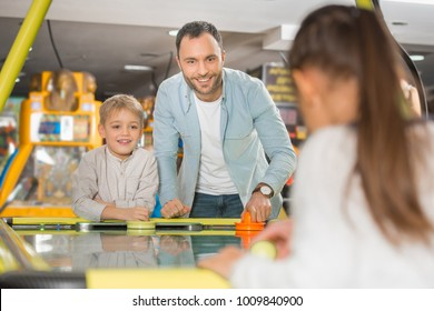 happy father with adorable little kids playing air hockey in entertainment center