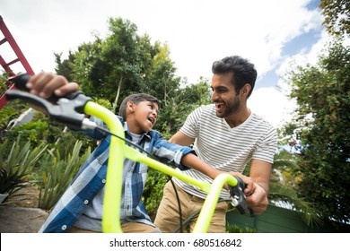 Happy father assisting son while riding bicycle against sky in yard