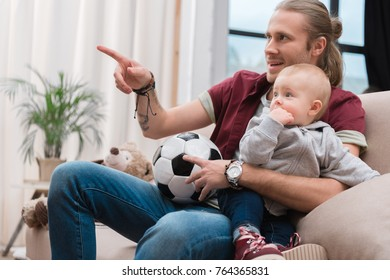 happy father with baby boy watching football match at home