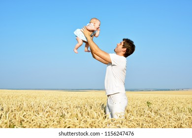 Happy father with baby outdoors. Dad playing with daughter in sunny summer day. Father holding child. Portrait on blue sky.