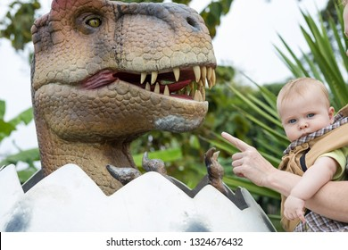 Happy father and baby son playing in the adventure dino park at the day time. People having fun outdoors. Concept of summer vacation and friendly family.