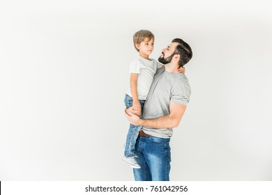 happy father carrying adorable little son isolated on white