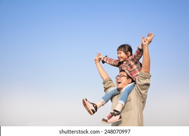happy Father carrying his daughter on shoulders with blue sky background
