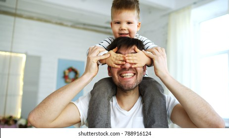 Happy father carrying his smiling son on neck in bedroom