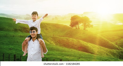 Happy father carrying his son on shoulders is on vacation and escape to nature. Fatherhood concept.