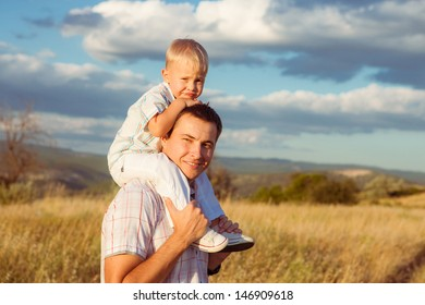 Happy father carrying his son on shoulders. Outdoors. Family Vacation