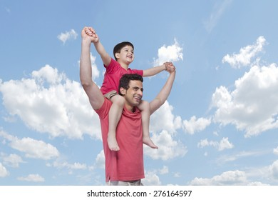 Happy father carrying son on shoulders against cloudy sky