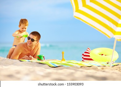 happy father and child having fun in sand on the beach