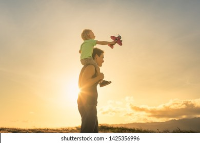 Happy father child moment. Father piggybacking his boy at sunset while he's playing with toy plane.