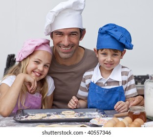 Happy father and children baking cookies together in the kitchen
