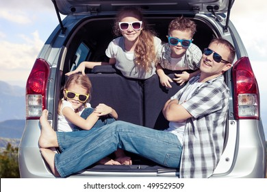 Happy father and children sitting in the car at the sunny day. Concept of friendly family on vacation.