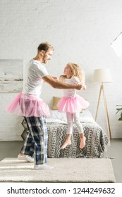 happy father and cute little daughter in pink tutu skirts dancing at home