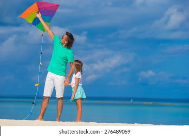 Happy father and cute little daughter flying kite together at tropical beach