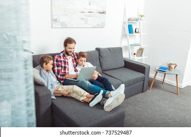 happy father with cute little sons using laptop together at home