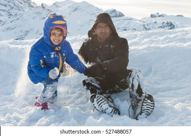 Happy father dad man daughter girl child kid Indian family tourists playing white snow in Engelberg, Mount Titlis, Switzerland. Enjoying vacation dayout winter in the sunlight Himalayan mountain.