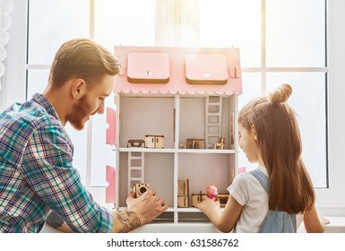 Happy father and daughter girl play with doll house at home. Funny lovely family is having fun in kids room.