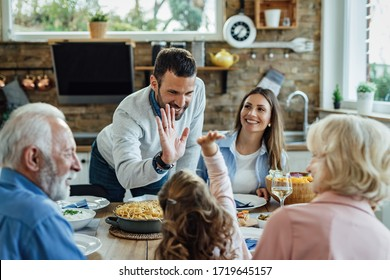 Happy father and daughter giving high-five to each other during a family lunch in dining room.