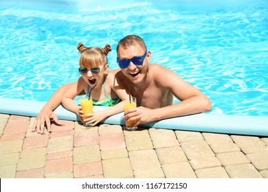 Happy father and daughter with glasses of juice resting in swimming pool