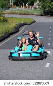 Happy father and daughter having fun on carting