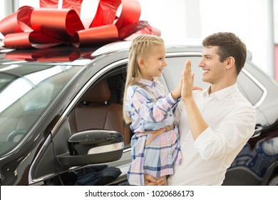 Happy father and daughter high fiving each other posing in front of their new car with a red bow on the roof copyspace buying present gift family happiness lifestyle travelling children parenthood