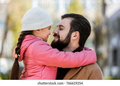 happy father with daughter hugging in autumn outfit and looking at each other. outside