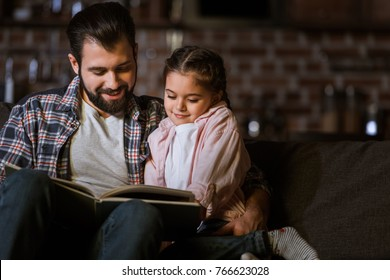 happy father with daughter hugging on couch and reading book at home