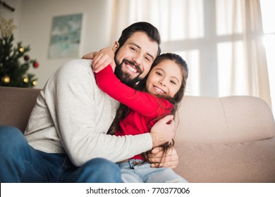 happy father and daughter hugging and sitting on sofa
