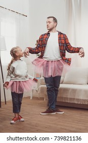 happy father and daughter in pink skirts dancing together at home