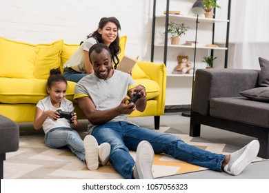 happy father and daughter playing video games while mother sitting on couch