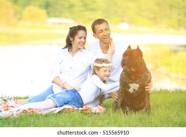 happy father of a daughter and a pregnant mom at a picnic