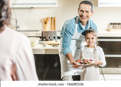 happy father with daughter showing plate with pancakes to mother at kitchen
