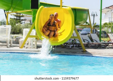 Happy Father and Daughter Sliding Down Water Slide
