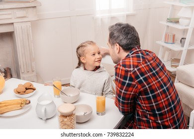 happy father and daughter smiling each other while having breakfast together