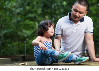 Happy father and daughter spending time together.Summer outdoor shot on a tropical garden.