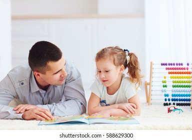 happy father and daughter spending time together by reading interesting book