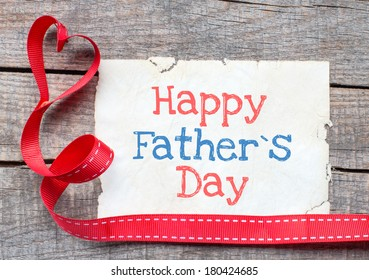 Happy father day on aged paper on wooden background
