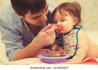 Happy father feeding baby girl on blanket at home