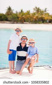 Happy father and his adorable kids outdoors sailing on yacht or catamaran