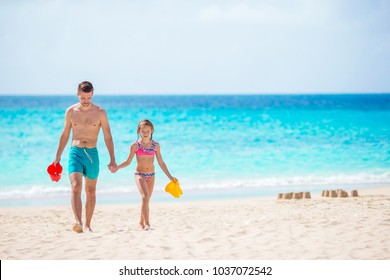 Happy father and his adorable little daughter at white sandy beach