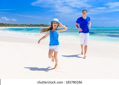 Happy father and his adorable little daughter having fun at tropical beach