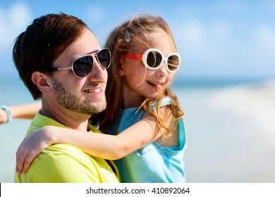 Happy father and his adorable little daughter outdoors at beach