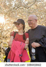 Happy father and his adult daughter enjoying leisure time in a spring park