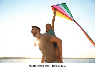 Happy father and his child playing with kite near sea. Spending time in nature