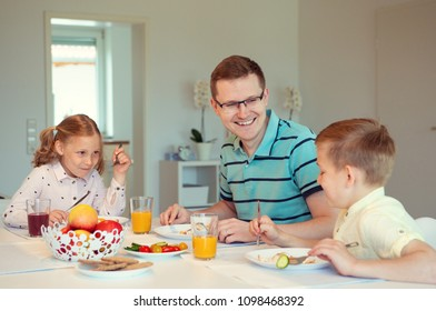 Happy father with his cute children talking at the breakfast at home