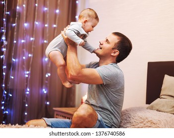 Happy father with his five mouth old dauhter playing at home on the bed. Portrait of a father with his baby - Image