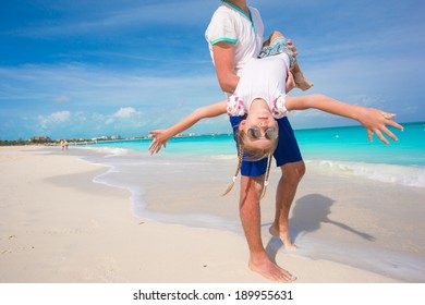 Happy father and his little cute girl enjoy summer vacation at perfect beach