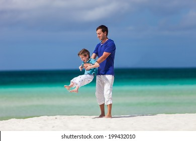 Happy father and his little son at tropical beach having fun during family summer vacation